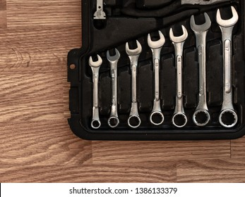 A tool kit laying on a wooden floor, exposing wrenches