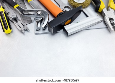 tool set of hammer, rulers, wrench and pliers on grey scratched metal background