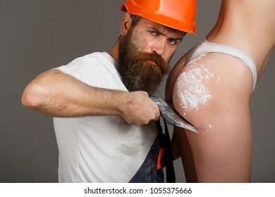 Tool, trowel, handyman, man builder. Ass, bum, butt. Builders in hard hat, helmet. Bearded man worker, beard. Female ass in underwear. Plastering tools. Naked body. gorgeous bum, sexy girl.