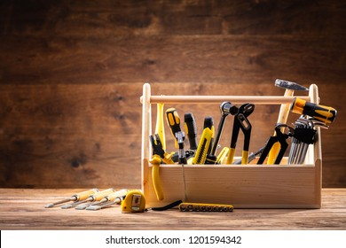 Toolbox With Various Worktools On Wooden Surface