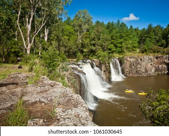 Tooloom Falls is a site of special cultural significance to the local Githabul People who know this place as Dooloomi. Multiple waterfalls surrounded by forest into large pond with two yellow canoes.