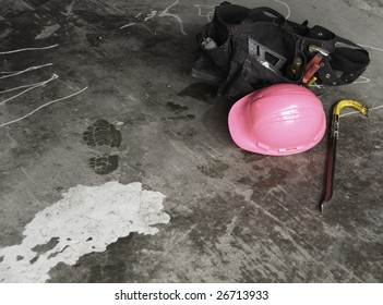 Tools along with a pink hardhat on the concrete floor.