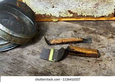 Tools for beekeeping and honey accessories. Beekeeping equipment, a set off new tools. Various beekeeping equipment on the old wooden table.
