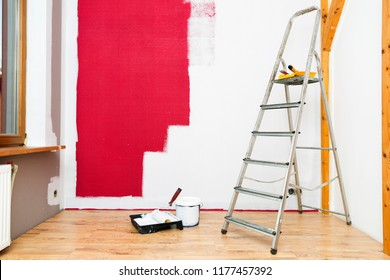 Tools for coloring, paint roller, brush, aluminium leader. Wall partly collored.