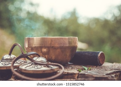 Tools for creating a calm state of mind and sound meditation. Singing bowl with bokeh in vintage style.