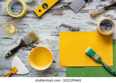 Tools for decorating and repairing house on grey wooden table background, top view. Yellow paint in bucket and brushes. Copy space.