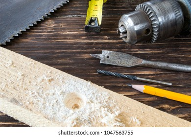 Tools for drilling on a wooden background.