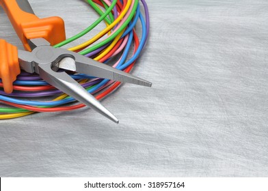 Tools for electrician and cables on grey metal surface