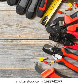 Tools of an electrician-installer or Builder on a gray wooden table. Construction tools for repair on a gray background. Top view with space for text