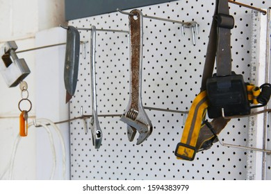 Tools hangings from a white pegboard