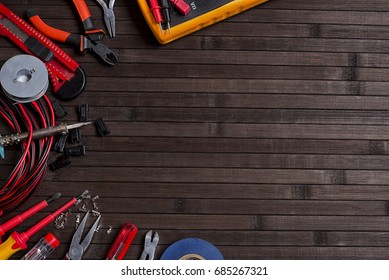 Tools for a home electrician, soldering wires and repairing on a dark background