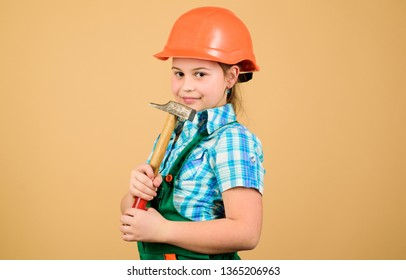 Tools to improve yourself. Repair. Future profession. Builder engineer architect. Kid worker in hard hat. Child care development. small girl repairing with hammer in workshop. she loves her job.