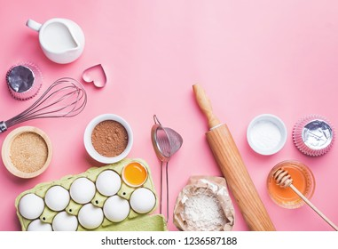Tools and ingredients for making sweet bakery like pie or cupcakes. Baking flat lay on pink background.