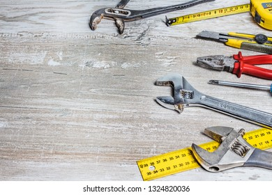 Tools: keys, pliers, screwdrivers lying on a wooden background. Background with free space and hydraulic tools.