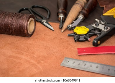 Tools for leather crafting and pieces of brown leather. Manufacture of leather goods.
