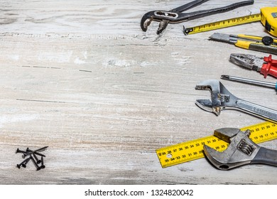 Tools lying on a wooden background. Background with tools and free space.