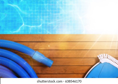 Tools for the maintenance of the pool on wooden slats. With pool with water and blue mosaics background and sunshine. Horizontal composition. Top view