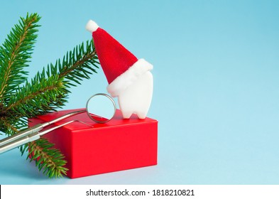 tools, mirror, probe, tooth in Santa hat on red podium for new year on blue background. creative medical stomatology christmas card. Health care, dental hygiene concept. free space