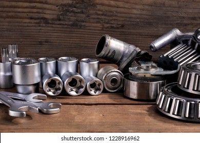 tools and old auto parts on wooden background