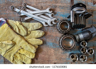 Tools, old auto parts and protective gloves