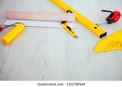 Tools on the floor for sticking wallpaper.