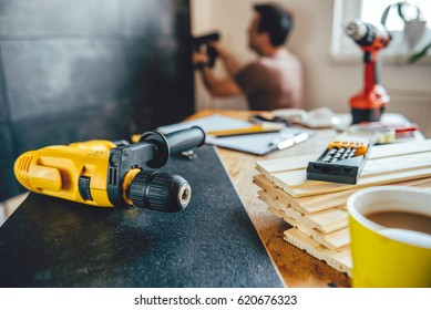 Tools on the table and man renovating wall in the background