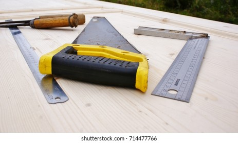 Tools on wooden surface, chisel, ruler, hacksaw