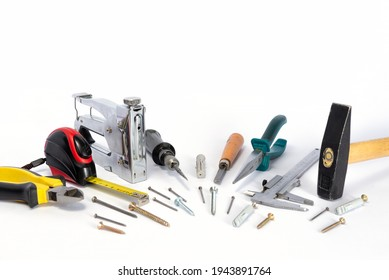 Tools and parts are on a white background. Metal object. A group of repair tools. Various parts and spare parts on the table. Tools for men. A set of working tools.