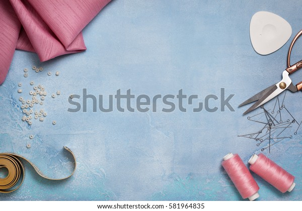 Tools for sewing: the fabric, scissors, pins, tape measure on blue concrete background (top view)