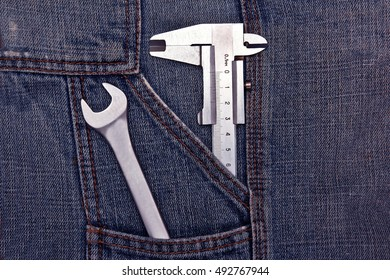 tools spanner and micrometer in jeans pocket