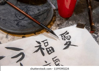 Tools and supplies used in learning traditional Chinese character calligraphy (for Xi An or west peace, hapiness and love) on tabletop in classroom.