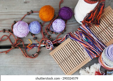 tools and thread for weaving on a wooden background top view