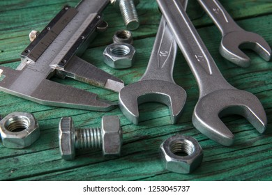 Tools. Wrenches, calibre, bolts and nuts on wooden background