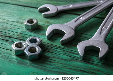 Tools. Wrenches and nuts on wooden background