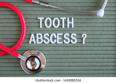Tooth abscess- text with a question mark on  green background with  stethoscope, medical concept diagnostics, treatment, healthcare.