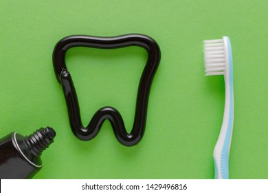 a tooth from black toothpaste, teeth care concept, toothbrush on green background
