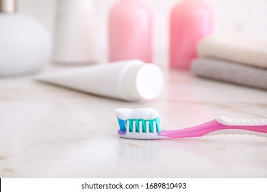 Tooth brush with paste on table in bathroom