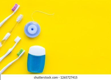 Tooth care with toothbrush, dental floss. Set of cleaning products for teeth on yellow background top view copy space