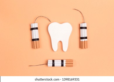 Tooth with cigarettes dynamite on yellow background. Smoking effect on human teeth. Dental care concept. Stop smoking, World No Tobacco Day.