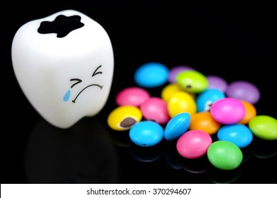 Tooth decay is crying with emotions sugar coated chocolate on the side. On a black background