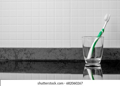 Tooth decay is in the glass near the sink. In the bathroom