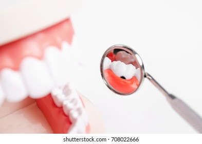 Tooth dental caries on denture with equipment dental on blue background.