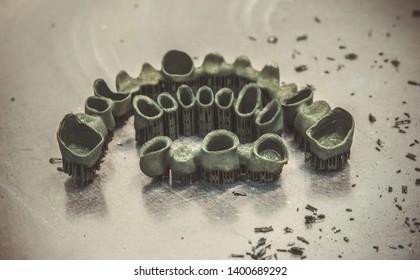 Tooth dental crowns created on 3d printer for metal way selective Laser Melting. Model created in laser sintering machine. DMLS, SLM, SLS additive technology. Concept of 4.0 industrial revolution.