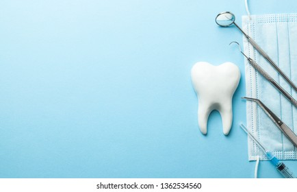 Tooth and dental instruments on blue background. Dental treatment. Dentist tools mirror, hook, tweezers, syringe. Copy space for text