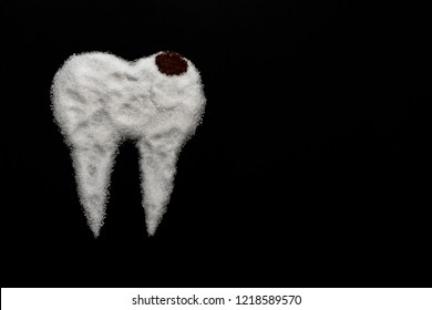 tooth made of sugar on a black background with caries