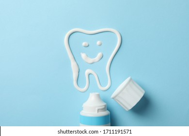 Tooth made of toothpaste and tube on blue background, top view
