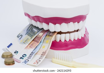 A tooth model with euro notes and brush isolated on white background