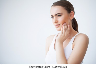Tooth Pain. Dental care and toothache. Woman Feeling Tooth Pain. Closeup Of Beautiful Sad Girl Suffering From Strong Tooth Pain. Attractive Female Feeling Painful Toothache. Dental Health And Care.