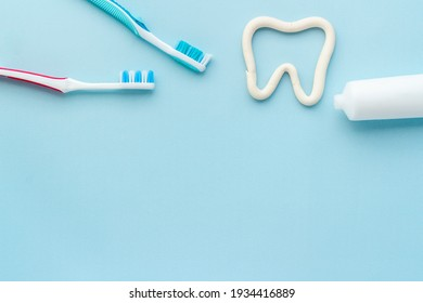 Tooth shape with tube of toothpaste and toothbrush. Dental hygiene concept, top view
