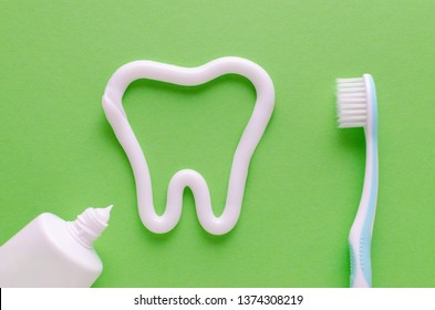 a tooth from toothpaste, teeth care concept, toothbrush on green background